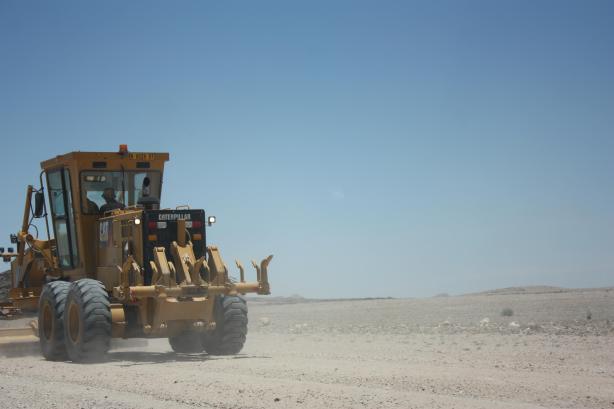 Un engin en train de remettre la route en état / A machine doing its best (I hope) to make this road smoother